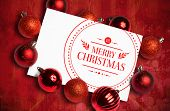 Banner and logo saying merry christmas against red paint splashed surface
