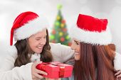 Mother and daughter with gift against blurry christmas tree in room