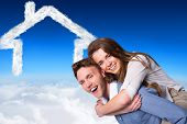 Smiling young man carrying woman against blue sky over clouds