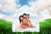 Family on the beach against green field under blue sky