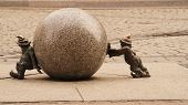 image of gnome  - Funny copper gnomes roll the stone ball - JPG