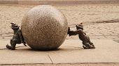 picture of gnome  - Funny copper gnomes roll the stone ball - JPG