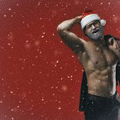 Cheerful Shirtless Santa On Snowy Red Backgrouund