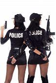 foto of cap gun  - Portret of two beautiful sexy policewomen with handcuffs in a black uniform that aiming a submachine gun - JPG
