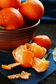 Fresh ripe mandarins on napkin, on dark wooden background