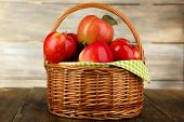 Wicker basket of red apples with green napkin on table and wooden background