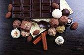 Bars of white and bitter chocolates with candies and sweet spoon on the dark wooden smooth background
