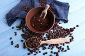 Brown bowl of ground coffee and coffee beans with wooden spoon and scoop on blue wooden background with jeans material