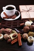 A Cup of coffee and a saucer with chocolate spoon and cute present, on the dark wooden smooth background