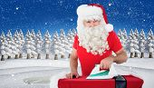 Happy santa claus ironing his jacket against snowy landscape with fir trees