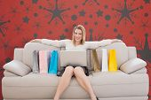 Blonde shopping online against snowflake wallpaper pattern