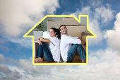 Bright couple with unpacking boxes moving to a new house against blue sky with white clouds