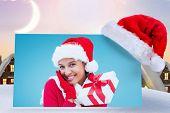 festive brunette holding gift against cute christmas village under crescent moon