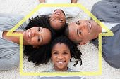 Smiling young family lying on floor against house outline