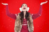 Brunette in winter clothes with hands out against red background