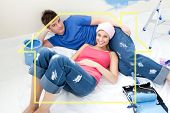 Young couple relaxing after painting a room in their new house against house outline