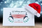 Colourful banner wishing a happy christmas against santa hat on poster