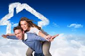 Smiling young man carrying woman against bright blue sky over clouds