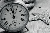 and old alarm clock and a star on a rustic wooden surface, in black and white