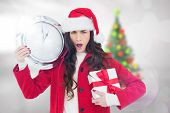 Surprised brunette holding a clock and gift against blurry christmas tree in room