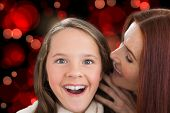 Mother and daughter telling secrets against red glowing dots on black