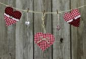 Red hearts and heart-shaped locks hanging on clothesline by distressed wood fence