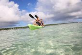 Couple canoeing in transparent caribbean sea