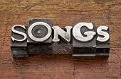 songs word in mixed vintage metal type printing blocks over grunge wood