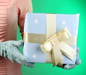 Gift box in female hand on color background