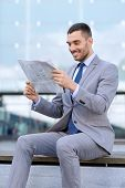 business, hot drinks and people and concept - young smiling businessman with newspaper over office building