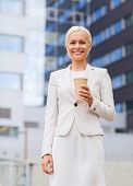 business, hot drinks and people and concept - young smiling businesswoman with paper coffee cup over office building