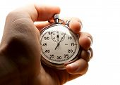 picture of stopwatch  - Male hand holding stopwatch on white in closeup - JPG