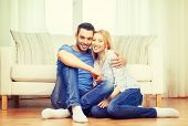 love, family and happiness concept - smiling happy couple sitting on floor at home