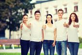advertising, friendship, education, school and people concept - group of smiling teenagers in white blank t-shirts showing thumbs up over campus background