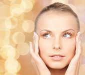 beauty, people and health concept - beautiful young woman touching her face over beige lights background