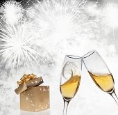 Golden gift box and champagne glasses on sparkling holiday background