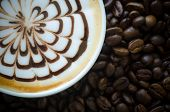 Closeup Of A Beautiful Cup Of  Latte Art On Coffee Bean Background