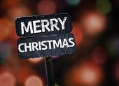 Merry Christmas sign with colorful background with defocused lights