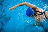 Female swimmer in an indoor swimming pool - doing crawl (shallow DOF)