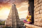 picture of mudra  - Woman with Namaste mudra sitting near Virupaksha temple in Hampi Karnataka India - JPG