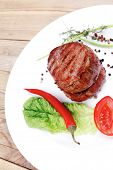grilled beef fillet pieces with thyme , red hot chili pepper and tomato on white plate over wood