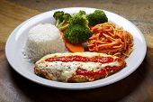 The steak parmigiana with pasta and rice