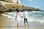 Bride And Groom Walking Together Holding Hands Near Sea, Sperlonga
