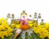 spa supplies with yellow orchid, oil, candle , salt in spoon ,on banana leaf