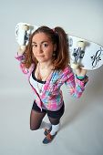 Young female holding a skateboard behind her head