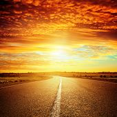 good red sunset and asphalt road to horizon