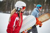 Young female and her boyfriend snowboarding on winter resort