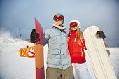 Female and male with snowboards having active leisure
