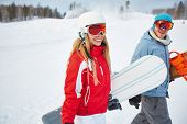 Young sporty couple with snowboards on winter resort