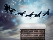 Composite image of santa flying his sleigh against snowy landscape with fir trees